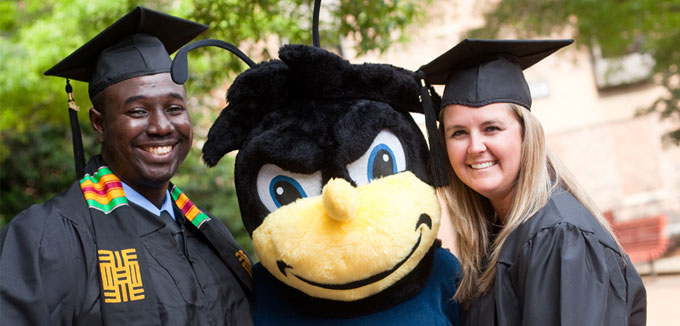 Smiling graduates at the commencement ceremony with the Eubie the UBalt bee.